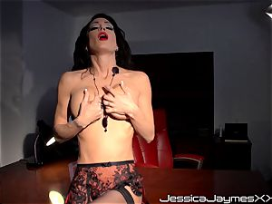 insane dark haired Jessica Jaymes thumbs her succulent cooch pie in her office