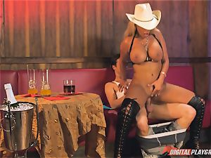 Bridgette B in steaming leather footwear and penetrates on a bed